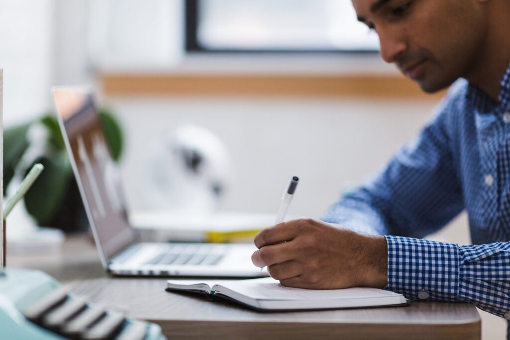 man researching on laptop and writing in notebook